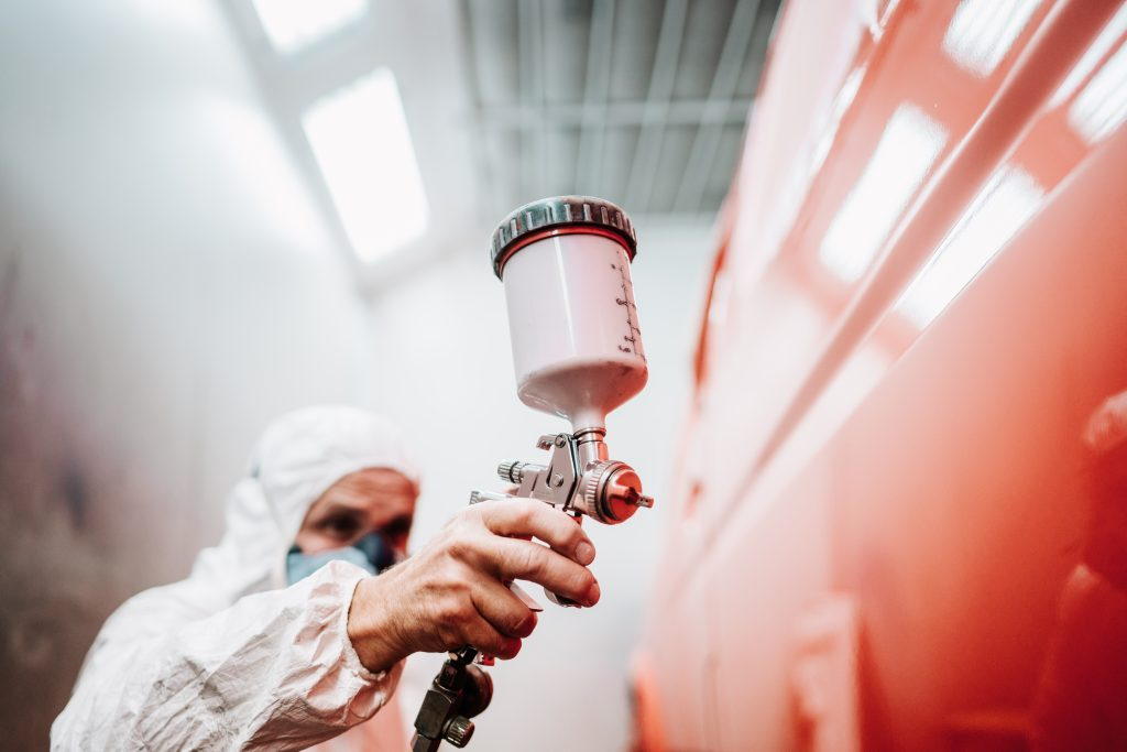Close,Up,Of,Paint,Spray,Gun,,Worker,Painting,A,Car
